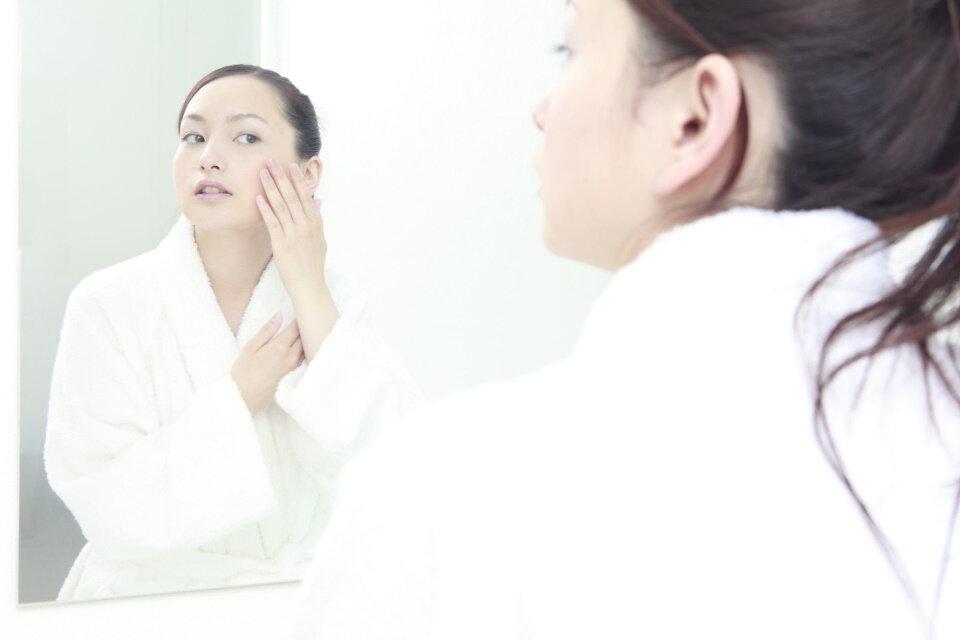 鏡で自分の顔をチェックしている女性