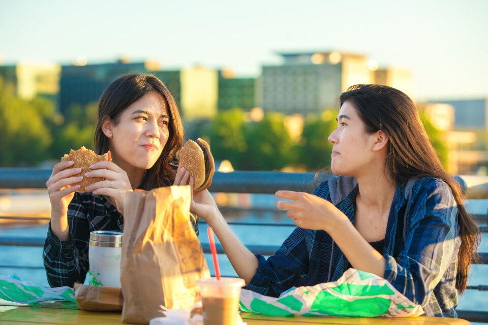 ファストフードを食べる若い女性たち