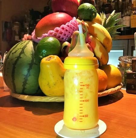 哺乳瓶に入ったマンゴーミルクのジンカクテル