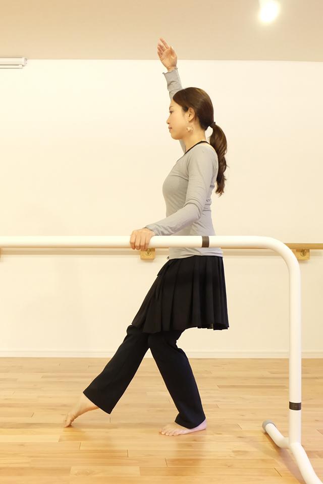 棒につかまりトレーニングを行う女性の写真